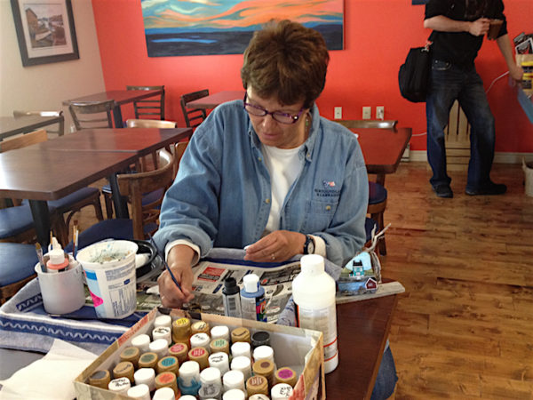 Artist Heidi Scarfone hand paints Twillingate beach rocks at the Blue Barrel