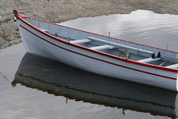 A hand-build wooden boat, likely a punt, a dory or a rodney, casting a reflection.