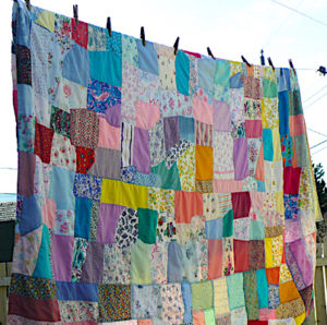 A traditional Newfoundland crazy quilt hangs on the line to dry.